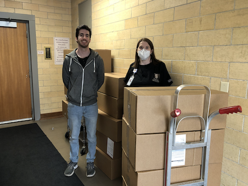 M3 Josh White is pictured with Robin Scott, the medical school's Occupational Health Manager, and a donation of 1,600 face shields.